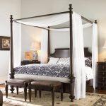 кровать с балдахином и квадратной конструкцией, рядом банкетки