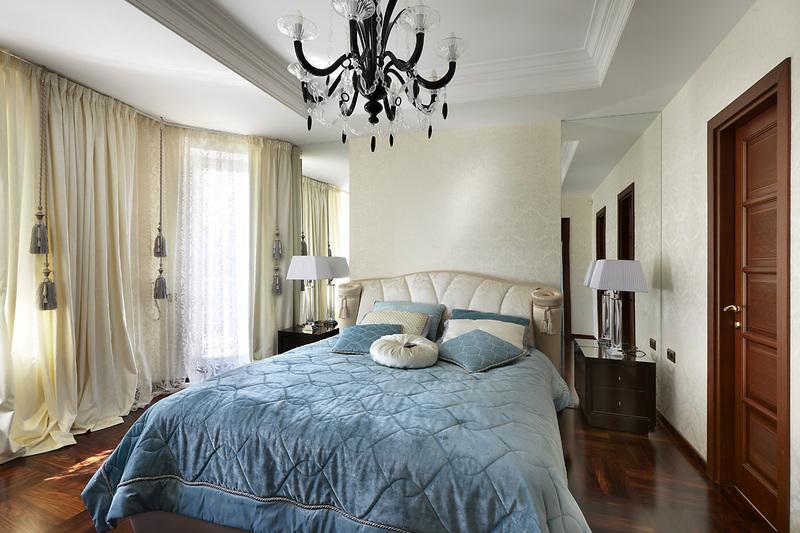 спальня неправильной формы с кроватью и голубым покрывалом