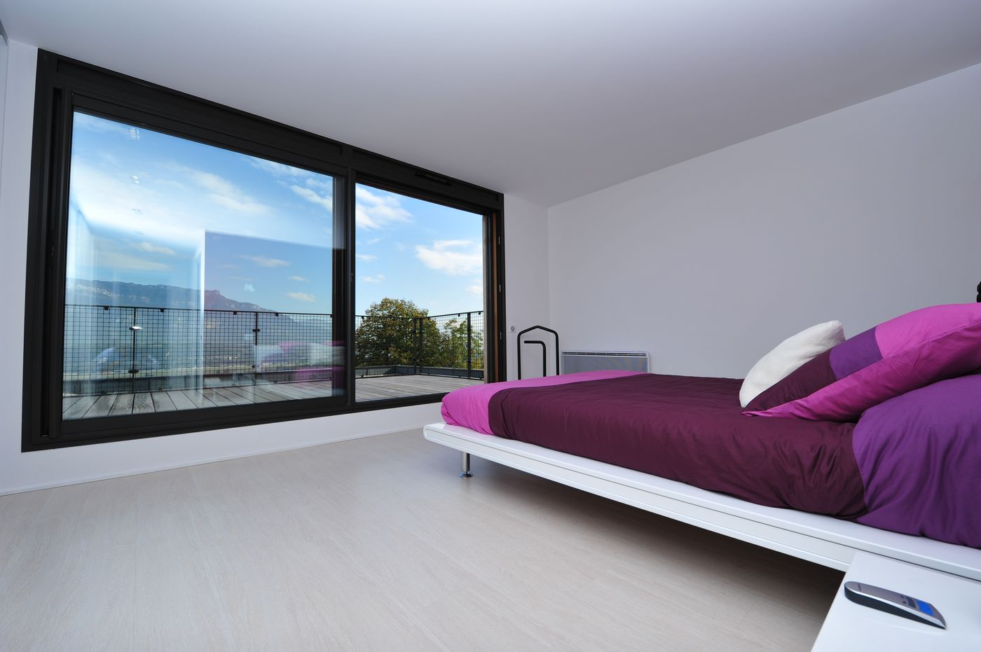 большое окно в спальне с фиолетовой кроватью