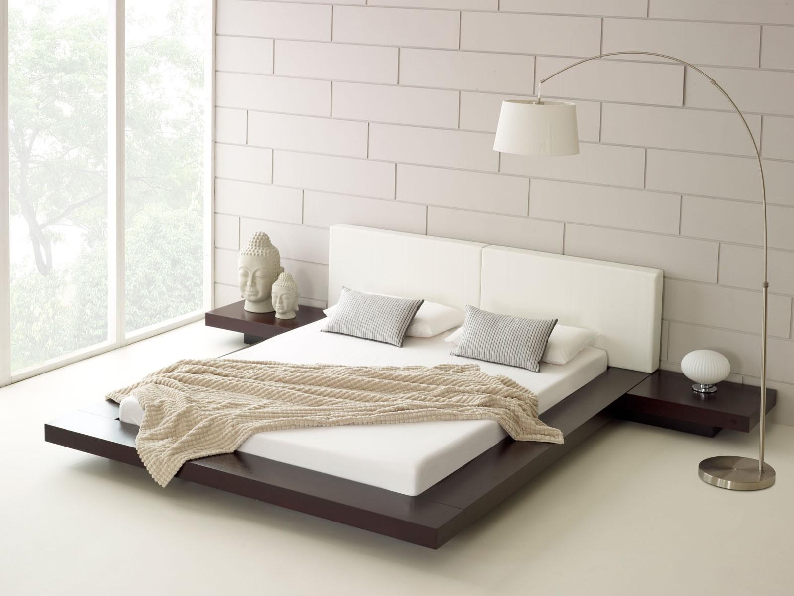 кровать с покрывалом и подушками в интерьере спальни в стиле минимализм