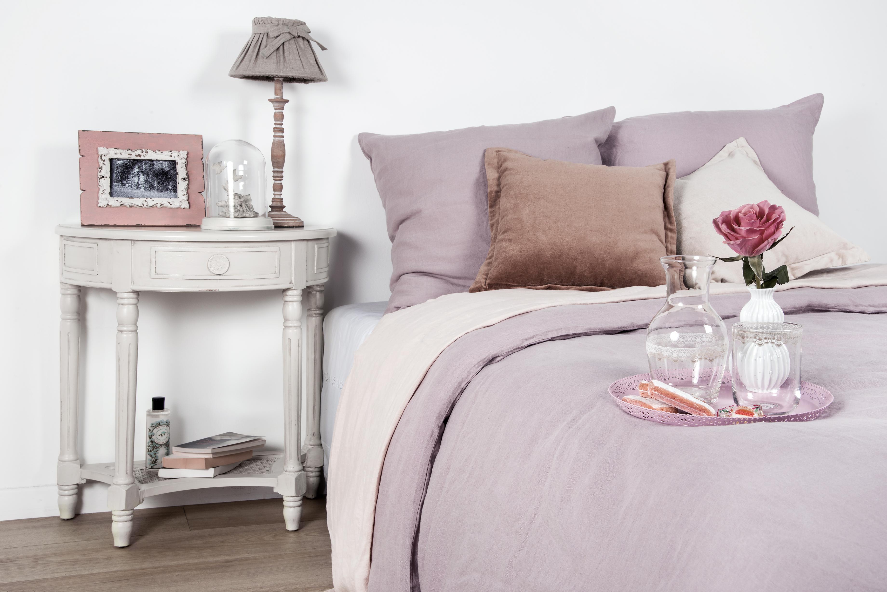 полукруглый деревянный столик у кровати с подушками