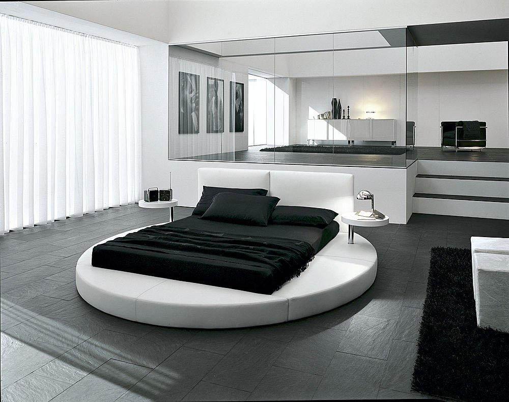 спальня с круглой кроватью и кабинетом за стеклом