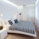 дизайн спальни в белых тонах с вязаным покрывалом на кровати
