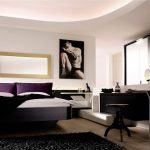 интерьер спальни с черной мебелью и постером на стене
