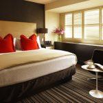 интерьер спальни с красными подушками на кровати