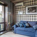 дизайн спальни с клетчатой стеной и синим диваном