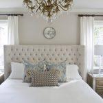 интерьер спальни с белой мебелью и золотистой люстрой