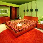 яркая спальня с салатовой стеной и оранжевым ковром