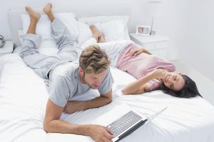 Man using a laptop next to his wife lying